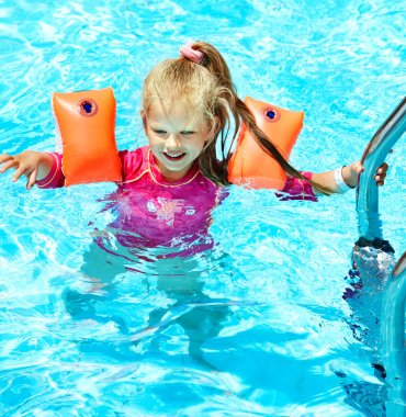 Child with armbands in swimming pool