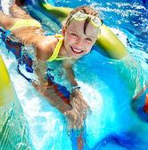 Fotografie Child on water slide at aquapark.