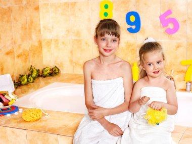 Children washing in bubble bath .