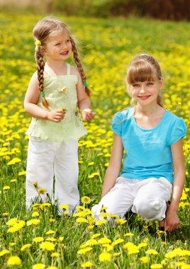 Children in field with flower.