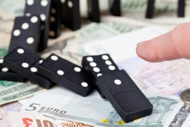 Finger on dominoes on bank notes