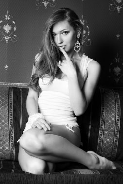 Pretty girl kneeling on the sofa