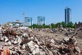 Hromadu trosek zřícené budovy na nové budovy pozadí
