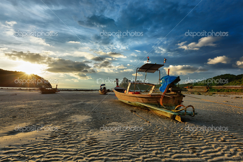 Long tail boat on beach on sunset