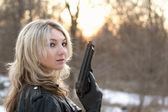 provokativní mladá žena s pistolí