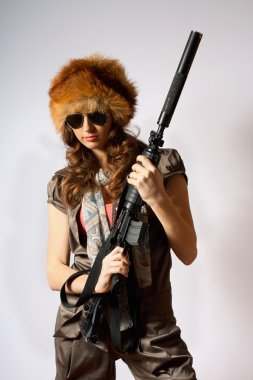 Beautiful girl in fur hat holding a rifle stock vector