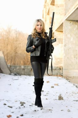 Blond smiling girl with gun