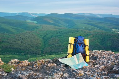 Map and tourist backpack in mountains