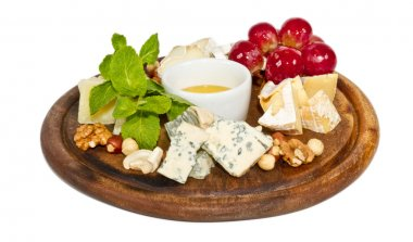 Various types of cheese with honey, nuts and grapes on plate, is