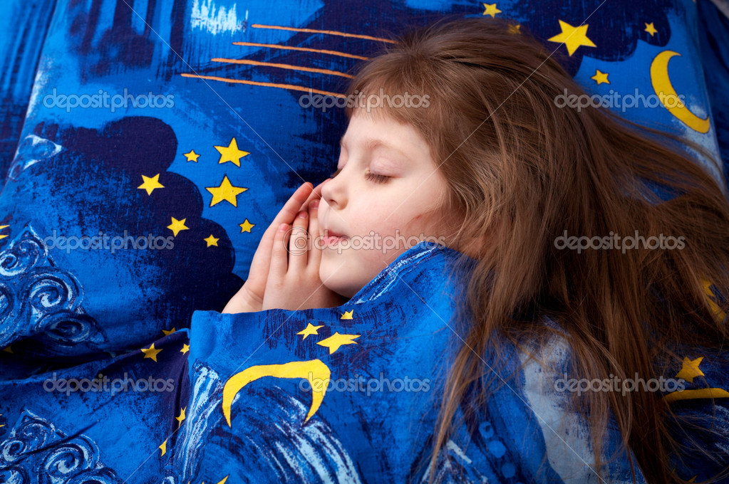 An image of little girl sleeping on a bed
