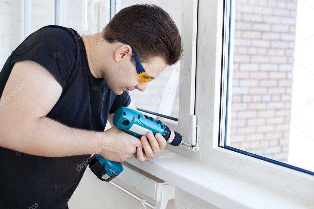 Man worker mounting window