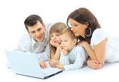 Fotografie liebevolle Familie sucht auf einem Laptop, liegend auf dem Bett zu Hause