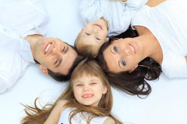 Happy family, mother, father and daughter resting on the white bed