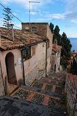 Malé ulice v sicilské město taormina sestupně směrem k moři
