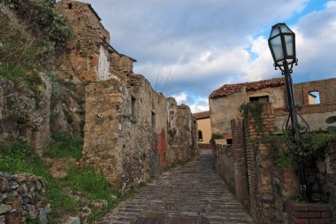 Paved medieval street with ruined house in Savoca village, Sicily