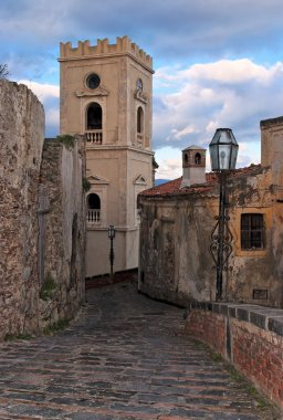 Paved medieval street with belfry in Savoca village, Sicily