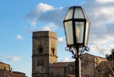 Medieval church and street lantern at sunset