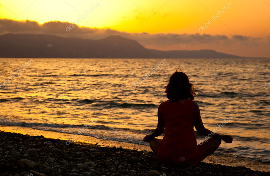 A woman is sitting in the lotus position on the beach