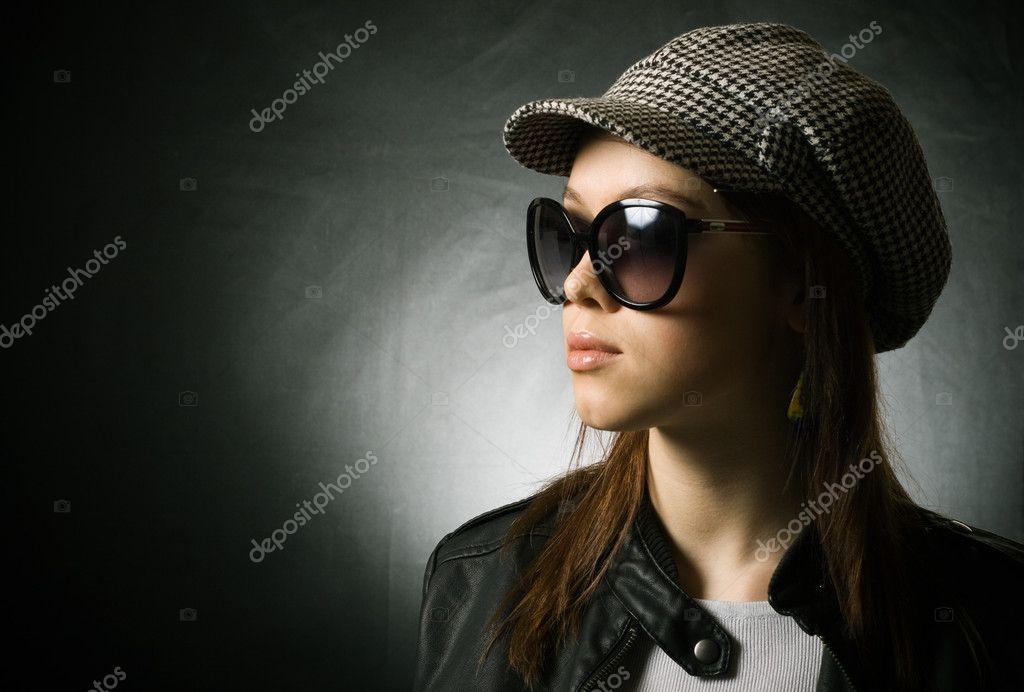 5f79b57172e09a Una bella ragazza con un cappello e occhiali da sole su sfondo scuro — Foto  di ...