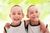 Dva usmívající se radost chlapci dvojčata