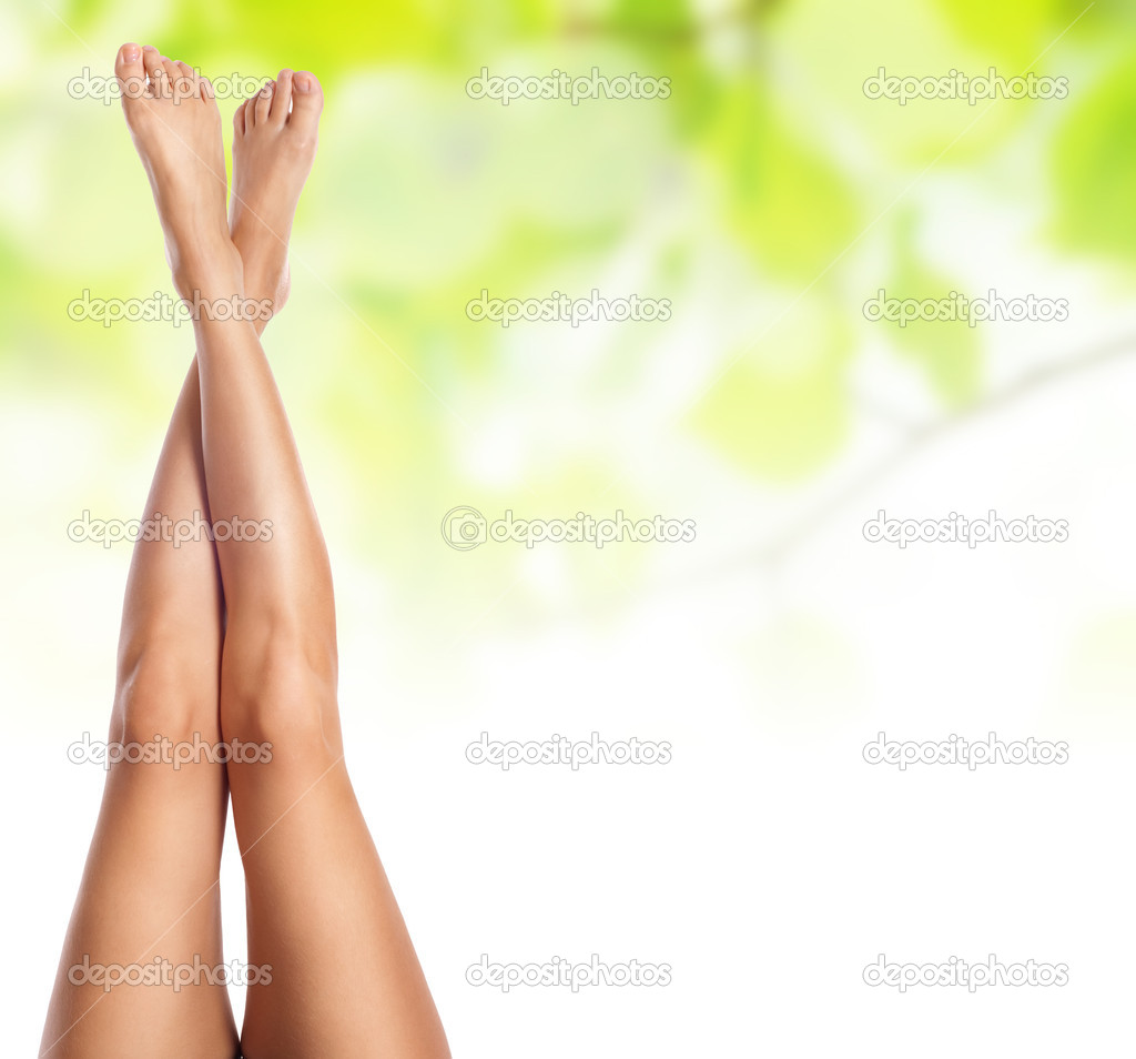 Healthy sexy slender female legs over green natural spring backg