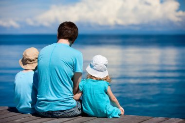 Father and kids sitting on wooden dock