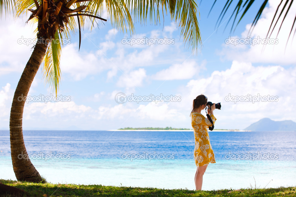Young woman taking photos at beach