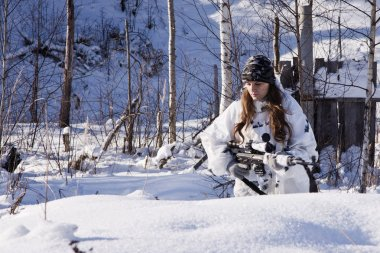 Sniper girl in white camouflage at winter forest.