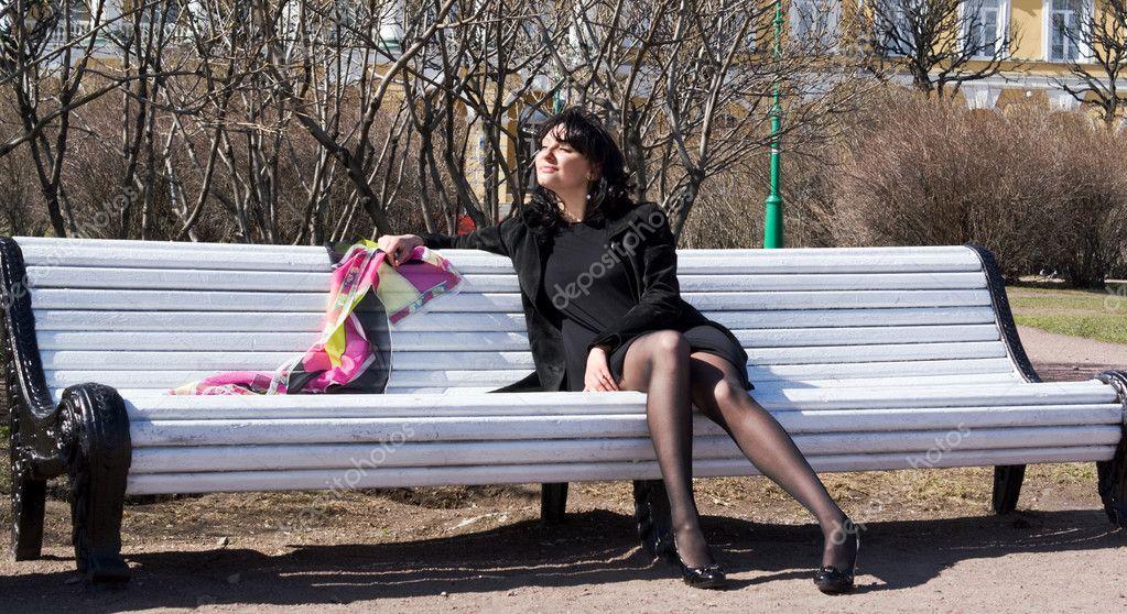 Belle brune aux longues jambes sur un banc au parc d été