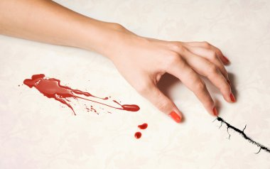 Woman's hand and a drop of blood
