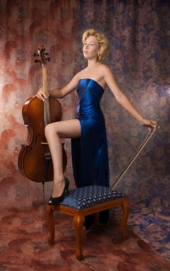 Woman in evening dress posing with cello