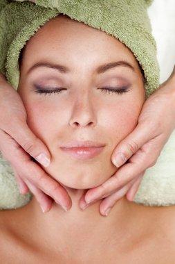 Young woman receiving facial massage