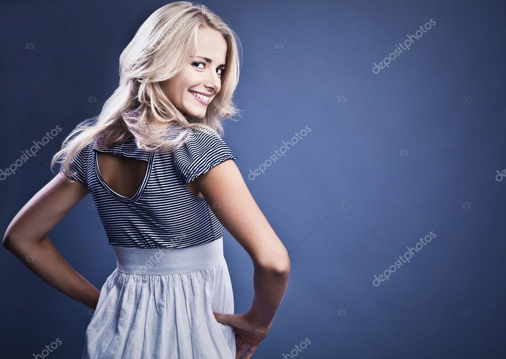 Studio fashion photo of beautiful young woman in elegance dress.
