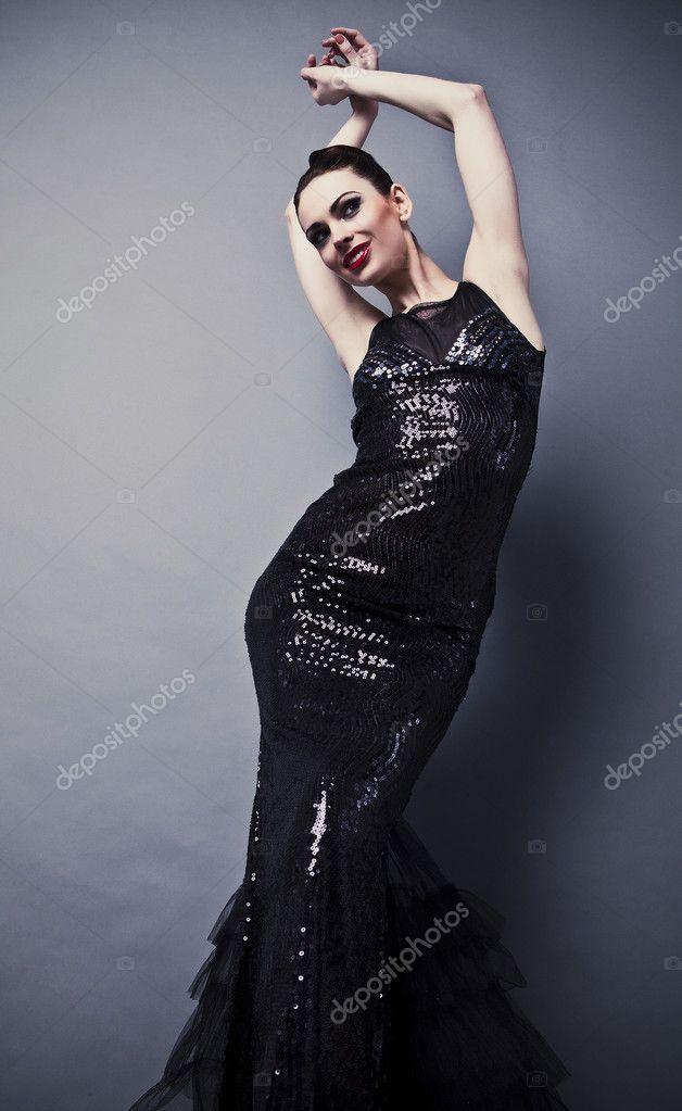 belle femme sur une robe classique noire pose en studio. Black Bedroom Furniture Sets. Home Design Ideas