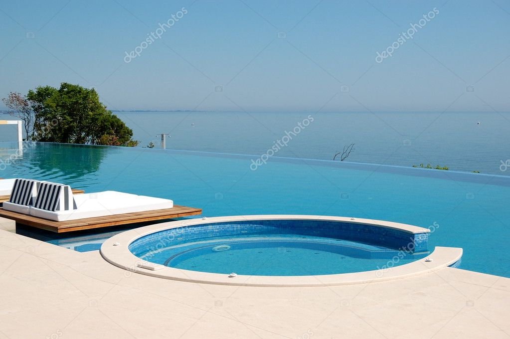 Infinity swimming pool with jacuzzi by beach at the modern luxu