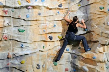 Woman on rock wall in sport centre