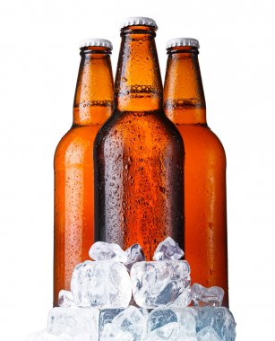 Three brown bottles of beer with ice isolated on white