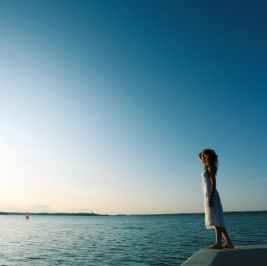 Beautiful girl standing on the shore waiting for a sailboat