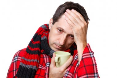 Cold man with flu wrapped in a warm blanket, holding a mug