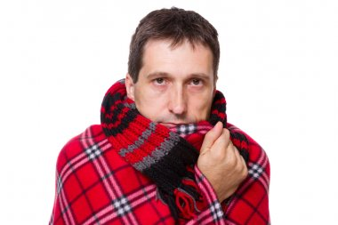 Man wrapped in a warm blanket shivering from the cold