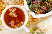 Fotografie Cup of healthy tea, mortar and pestle with healing herbs