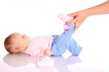 Mother putting shoes on baby