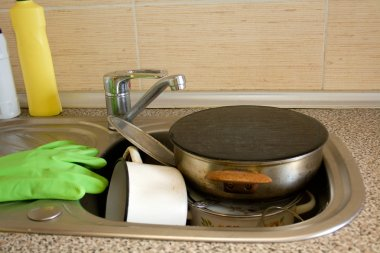 Pile of dirty dishes like plates, pot and cutlery in the sink