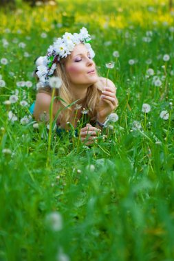Young woman blowing a dandelion on fields