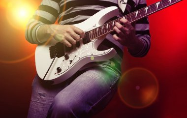 Young male musician with a white guitar