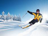 Fotografie lyžař v horách, připravené sjezdovky a slunečný den