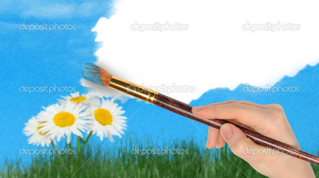 The hand with a brush draws a landscape
