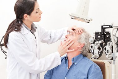 Optometrist taking an eyesight test examination. stock vector