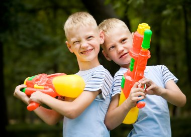 Two smiling twin brothers with water guns