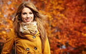 Fotografie Young woman with autumn leaves in hand and fall yellow maple gar